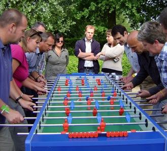 mensen spelen een potje tafelvoetbal in de open lucht