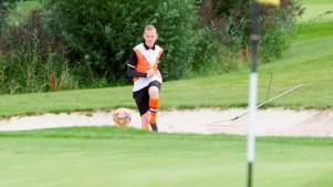 jongeman schiet bal uit de bunker bij voetbalgolf